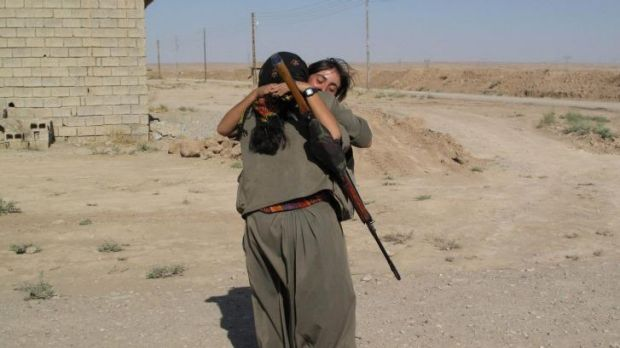 PKK fighters returning to their unit at the Daquq PKK base embrace after a night on the frontline.