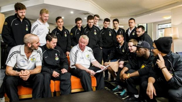 Tuggeranong United players talk strategy with coach Steve Forshaw in the lobby of the Alpha Hotel ahead of their match ...