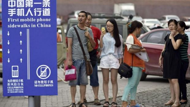 "Residents look at a sign with the words ""China's First Cellphone Lane"" explaining the use of a lane which separates ..."