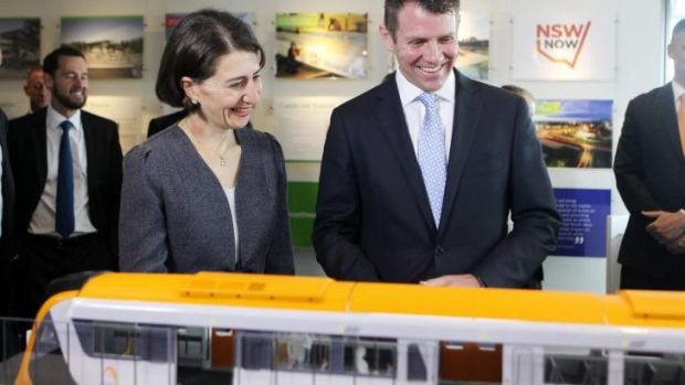All aboard: Mr Baird and Ms Berejiklian study a model of the new trains.