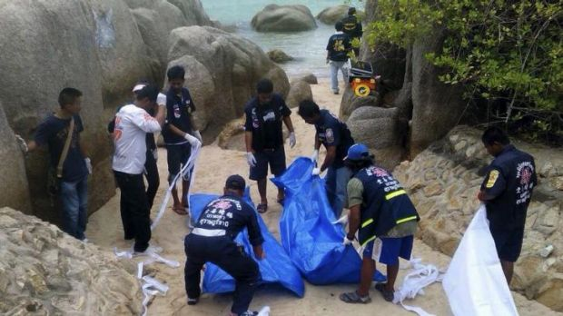 Thai officers work near the bodies of two British tourists found murdered on a Thai beach.