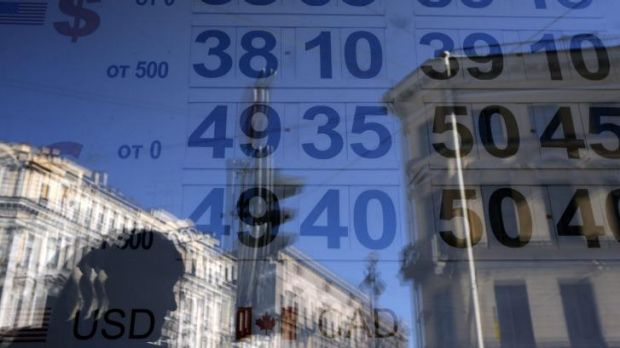 Ruble falling ... A woman is reflected in a window with a board displaying currency exchange rates in St. Petersburg.