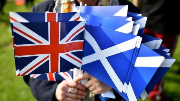 """A """"no"""" vote supporter holds Union and Scottish flags ahead of the Grand Orange Lodge of Scotland march in Edinburgh."""