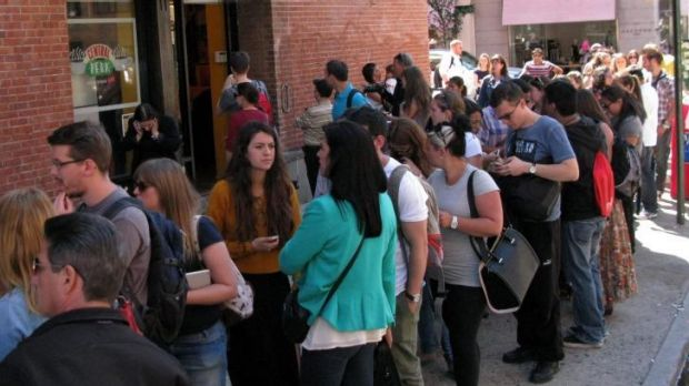 "Tourists line up outside a temporary ""pop up"" reproduction of the ""Central Perk"" coffee shop."
