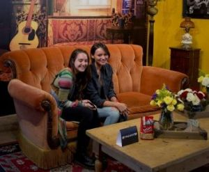 Visitors pose for a photograph on a couch at the Central Perk.