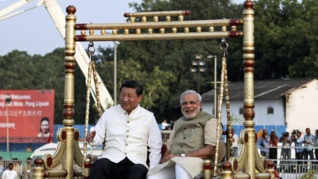 Chinese President Xi Jinping and Indian Prime Minister Narendra Modi sit on a traditional swing by the Sabarmati River ...
