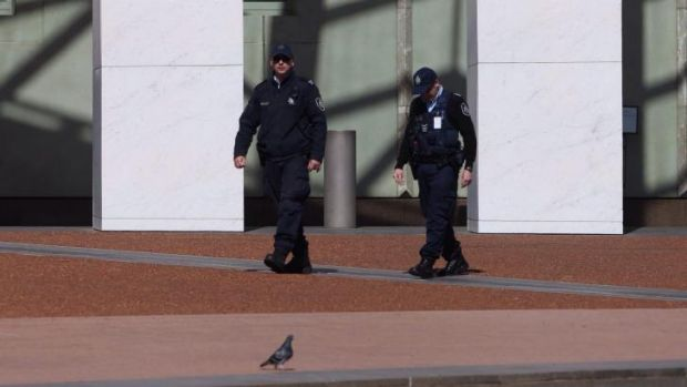 Australian Federal Police officers patrol Parliament House after terrorist threats escalated security concerns.