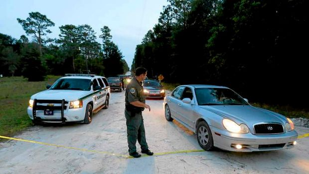 An officer lowers police tape to let cars through at the scene of the shooting in Bell, Florida.
