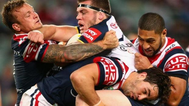 All in: Ethan Lowe of the Cowboys gets to grips with Aidan Guerra of the Roosters.