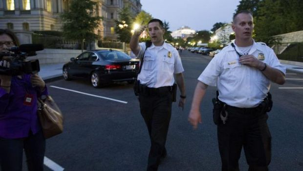 Secret Service police give instructions as they evacuate the White House minutes after President Barack Obama departed ...