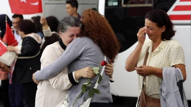 An employee at Turkey's consulate in the northern Iraqi city of Mosul is welcomed by family at Esenboga airport in ...