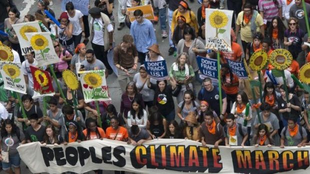Activists hold a banner as they lead a march of tens of thousands down 6th Avenue during the People's Climate March ...