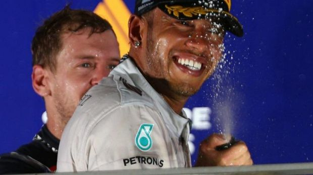 Winner: Lewis Hamilton is soaked with champagne by Sebastian Vettel.