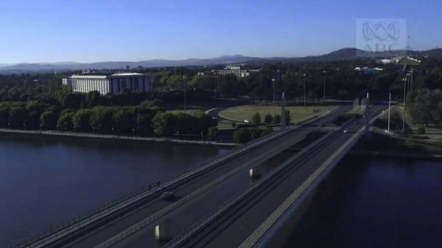 The opening shot of Canberra in Episode 1 of The Code: an aerial view of a car crossing Commonwealth Avenue bridge ...