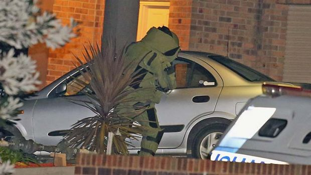 A police officer in a bomb suit inspects the car at the scene.