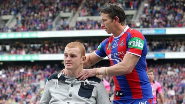 Kurt Gidley comforts Alex McKinnon before the start of the round 19 match between the Knights and theTitans.