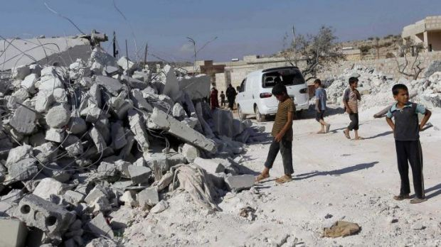 Residents inspect damaged buildings in what activists say was a US strike, in Kfredrian, Idlib province.