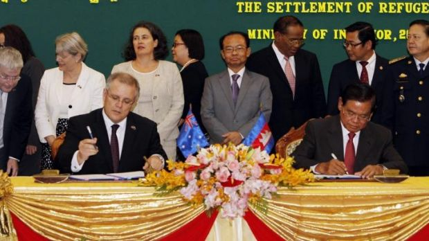 Scott Morrison and Cambodian Interior Minister Sar Kheng signing the agreement.