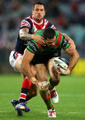 Unstoppable force: Greg Inglis powers through the tackle of Mitchell Pearce.