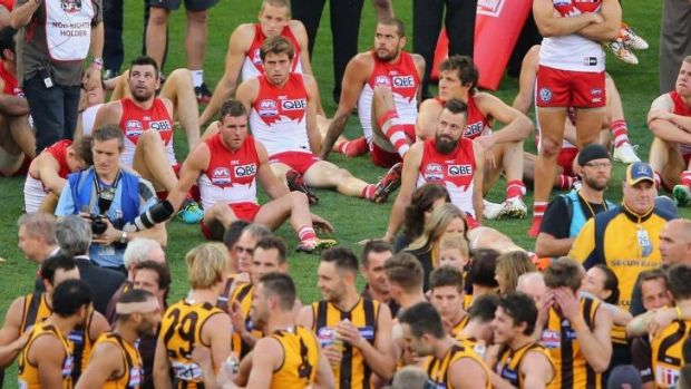 Two halves: Sydney players look on as Hawthorn celebrates its victory.