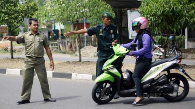 Police officers check a female motorcyclist wearing pants at a checkpoint in Aceh.