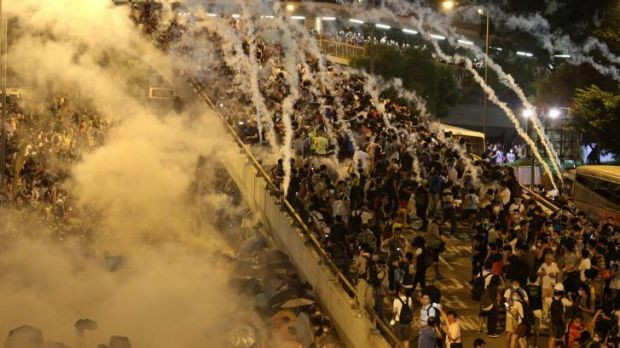 Rapid response: Police fire tear-gas as crowds of demonstrators grow.