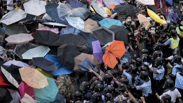 Makeshift shield: Protesters hold up umbrellas to try to protect themselves from tear-gas as pro-democracy demonstrators ...
