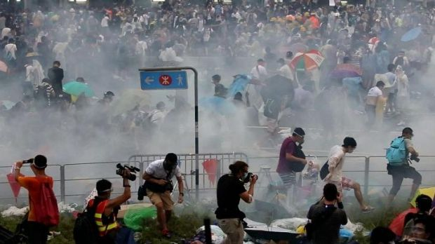 Protesters flee tear-gas near Hong Kong's government headquarters.