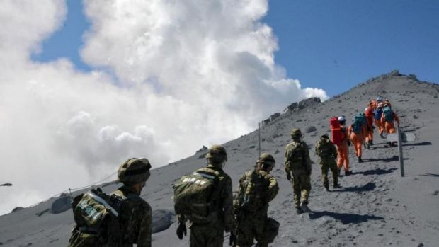 Japan's Self Defense Force soldiers and rescue workers search for survivors on the ash-covered top of Mount Ontake.