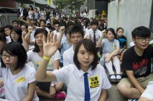 A secondary school student holds up a hand with a yellow ribbon tied around her wrist.