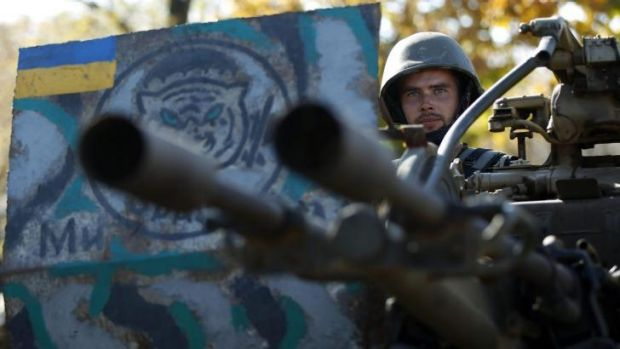 Uneasy truce: A Ukrainian serviceman sits at his anti-aircraft heavy machine gun at a military camp near the town of ...