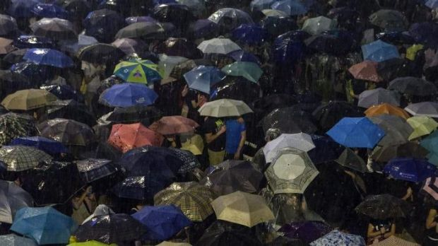 Pro-democracy protestors use umbrellas to shield themselves from heavy rain in Hong Kong.