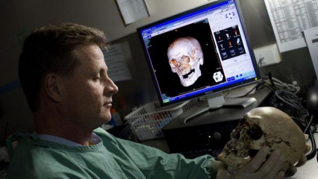 Dr Richard Bassed holds the skull, with its photo-superimposition on the screen behind him.