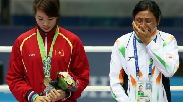 Sarita Devi is in tears as she stands on the podium.