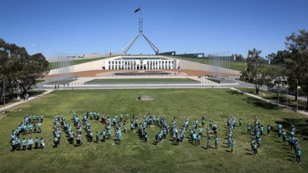 More than 350 young Australians form the words End Poverty on the lawns in front of Parliament House.