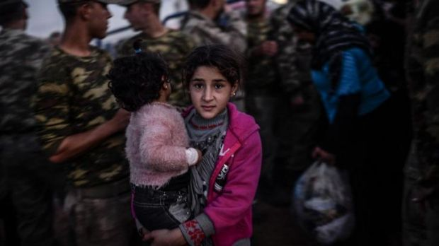 Running for their lives: Syrian Kurdish people arrive at the border with Turkey. Tens of thousands have fled into Turkey ...