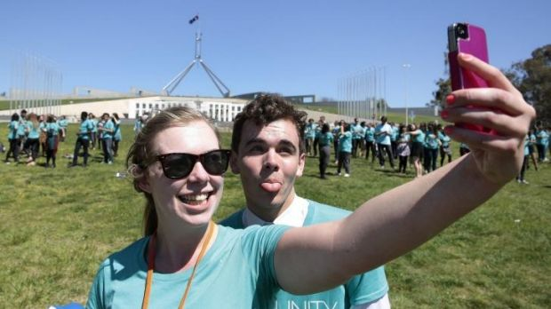 Liz Rhodes takes a selfie of her and Darcy Lower as 350 young people get into formation to spell out their anti-poverty ...
