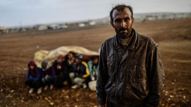Seeking safe haven: A Syrian Kurdish man stands next to other refugees taking cover from the rain.