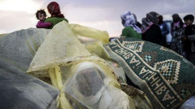 Misery: Syrian Kurds take cover from the rain after crossing the border between Syria and Turkey.