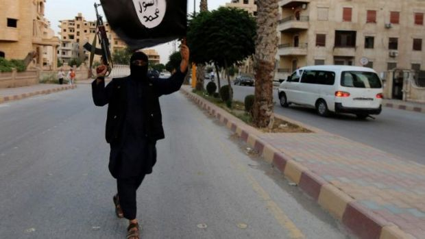 A member loyal to the Islamic State in Iraq waves an ISIL flag in Raqqa.