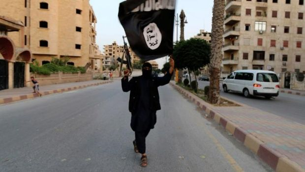 A member loyal to the Islamic State waves an ISIL flag in Raqqa.