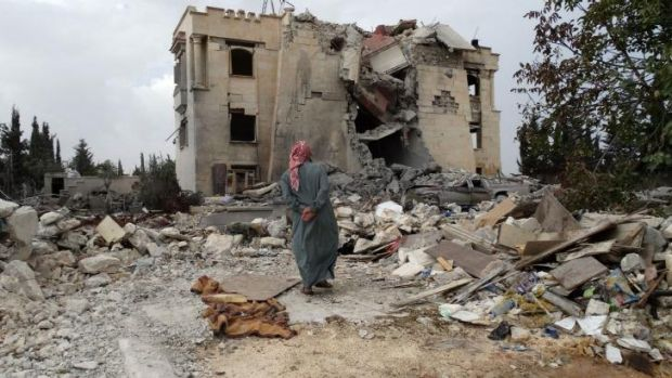 A Syrian man inspects the damage following a US-led coalition air strike.