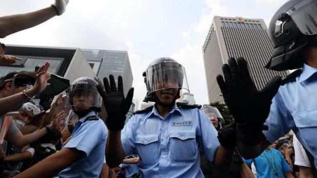 Police officers gesture as demonstrators gather outside the Central Government Offices.