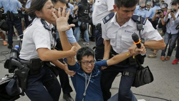 A pro-democracy protester is taken away by police officers in Hong Kong.