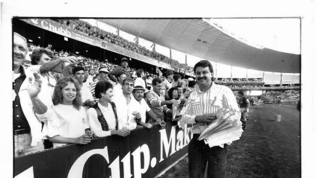 Canberra Times journalist Brad Turner hands out 'We Did It' posters after the Raiders win the 1989 grand final.
