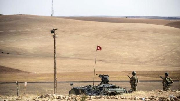 Turkish soldiers stand on a hill, facing IS fighters' position 10 kilometres west of the Syrian border town of Kobane.