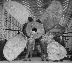 Dwarfed but standing tall: 1950s dockyard tradesmen pose with a single-mould brass propeller.