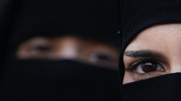 Two women wearing Islamic niqab veils stand outside the French Embassy in London during a demonstration in 2011.