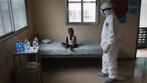 LONELY WAIT: A Liberian health worker dressed in an anti-contamination suit speaks with a boy at a centre for suspected ...