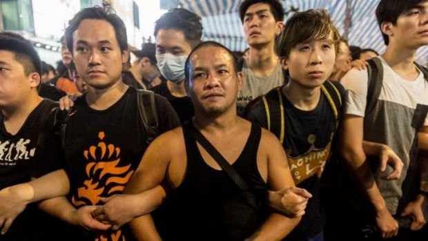 STRENGTH IN NUMBERS: Pro-democracy protesters form a human chain to guard a tent being used by them in the Kowloon district.